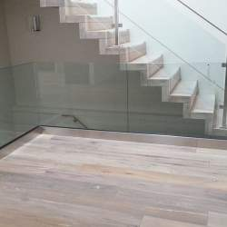 basement staircase with frame less glass railings
